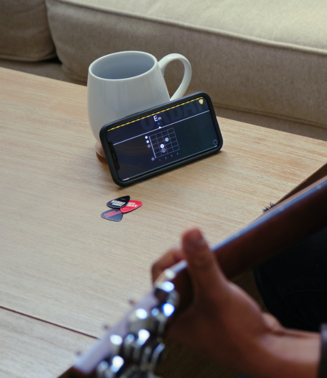 A person practicing guitar using the Urban App on their phone sitting on a coffee table.