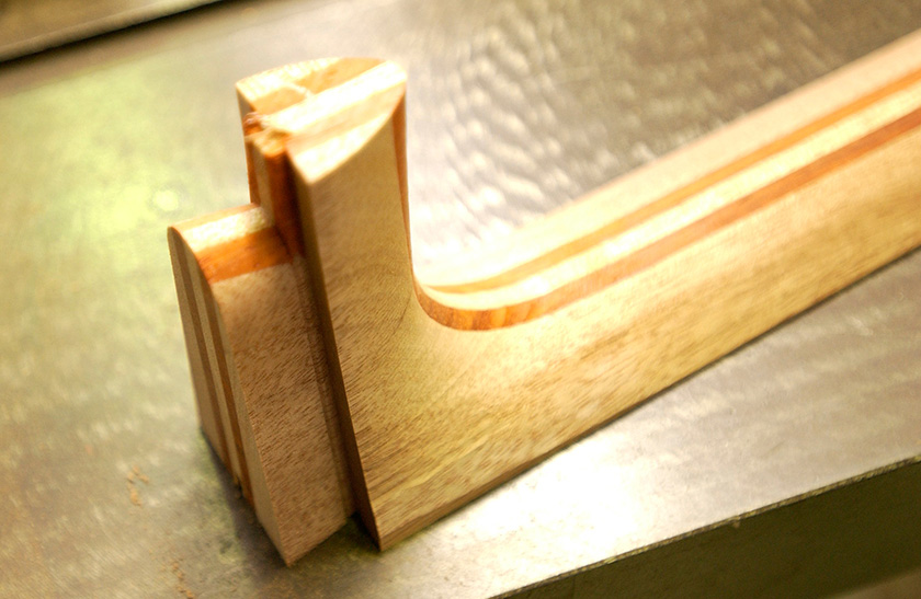 A neck carved to make a dovetail joint; the body it will connect to will be similarly carved