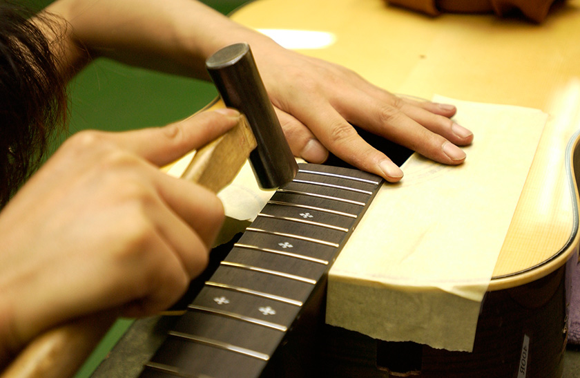 Frets are hammered into the fingerboard