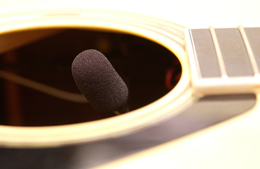 A condenser microphone placed inside a guitar
