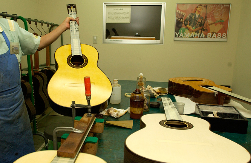 A guitar before the application of shellac on the right, and a guitar with glossy coating being held up on the left