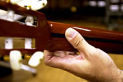 Four fingers are used to pluck the strings, with the thumb acting as a support.