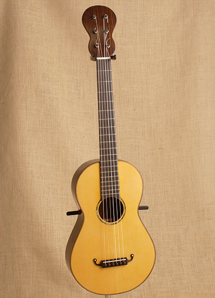 A fully restored nineteenth century guitar, showing the unique shape of the neck.