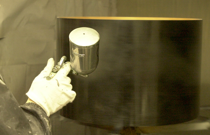 Paint is applied with a sprayer to give a flat black finish.