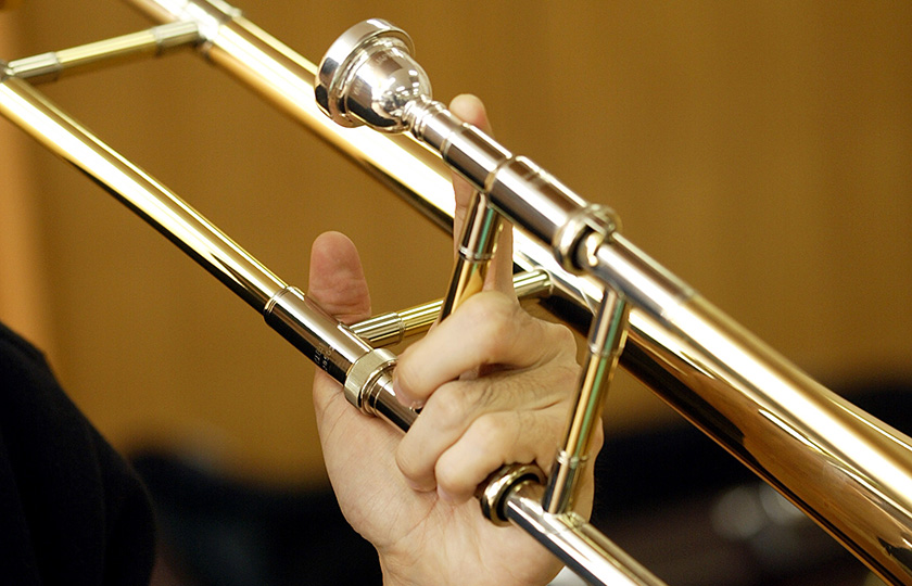 A trombone is held with the left hand and played with the right hand