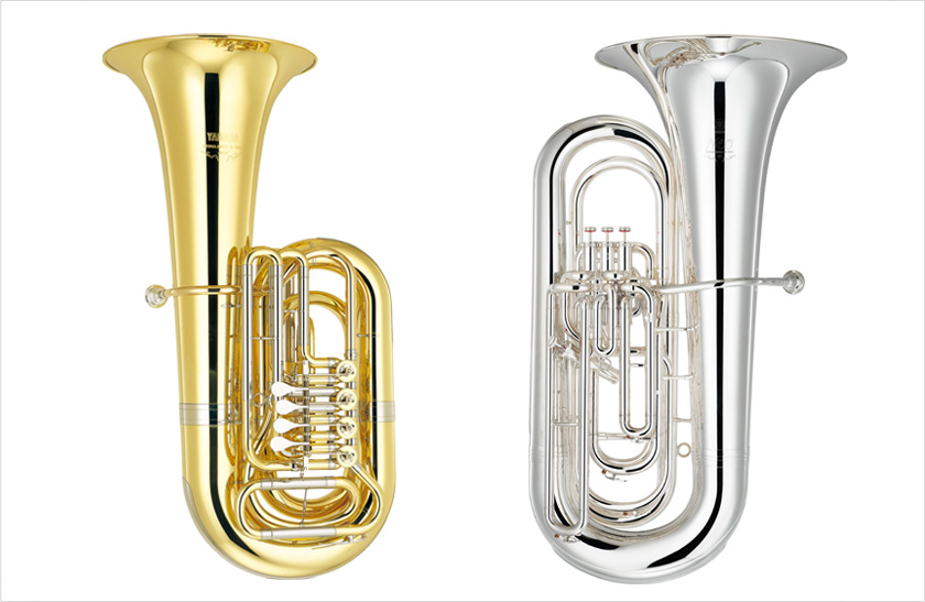 On the left is a brass tuba with a clear lacquer finish; on the right is a brass tuba with silver plating.