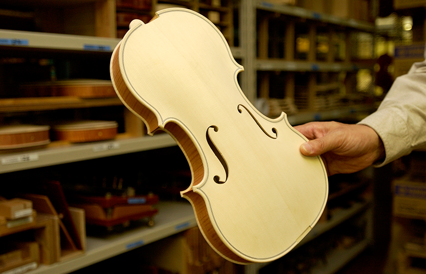 A white violin before the neck is attached