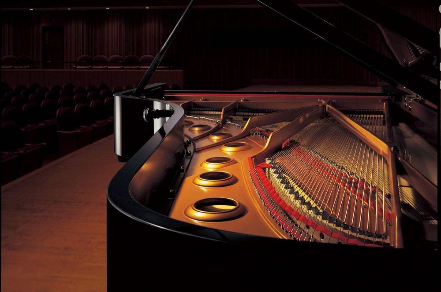 View of interior of a Yamaha concert grand on stage in an empty concert hall.