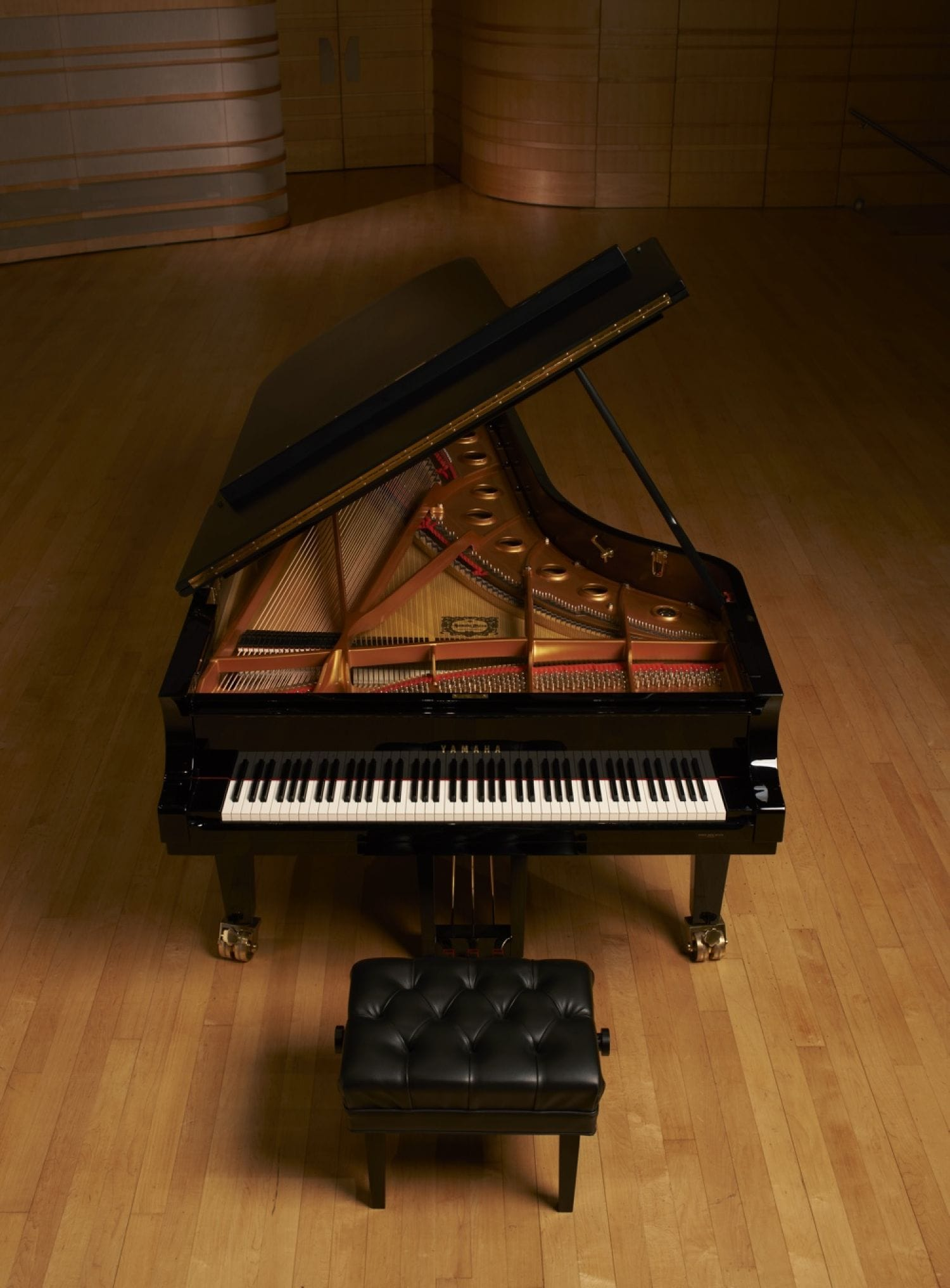 A view of a Yamaha concert grand with the lid open and view of keys and inner workings on an otherwise empty stage.