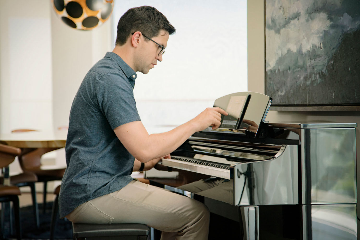 A man approximately 40 years old is smiling broadly while playing from sheet music on a Yamaha upright piano in a living room setting.