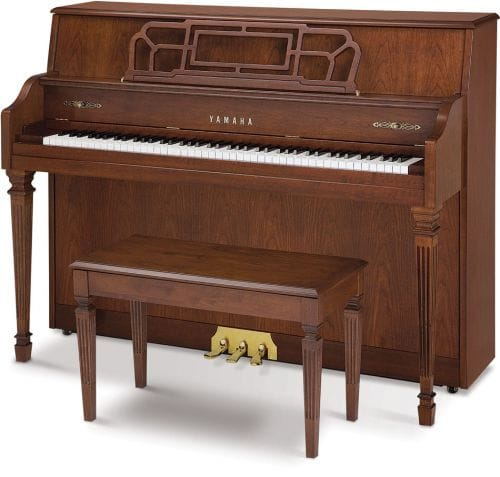 Yamaha upright piano and bench in a more traditional furniture style with squared legs with grooves.