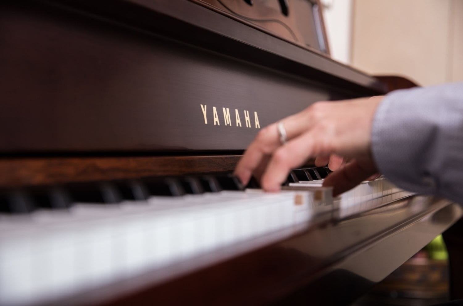 Closeup from side angle of man's hands playing piano.