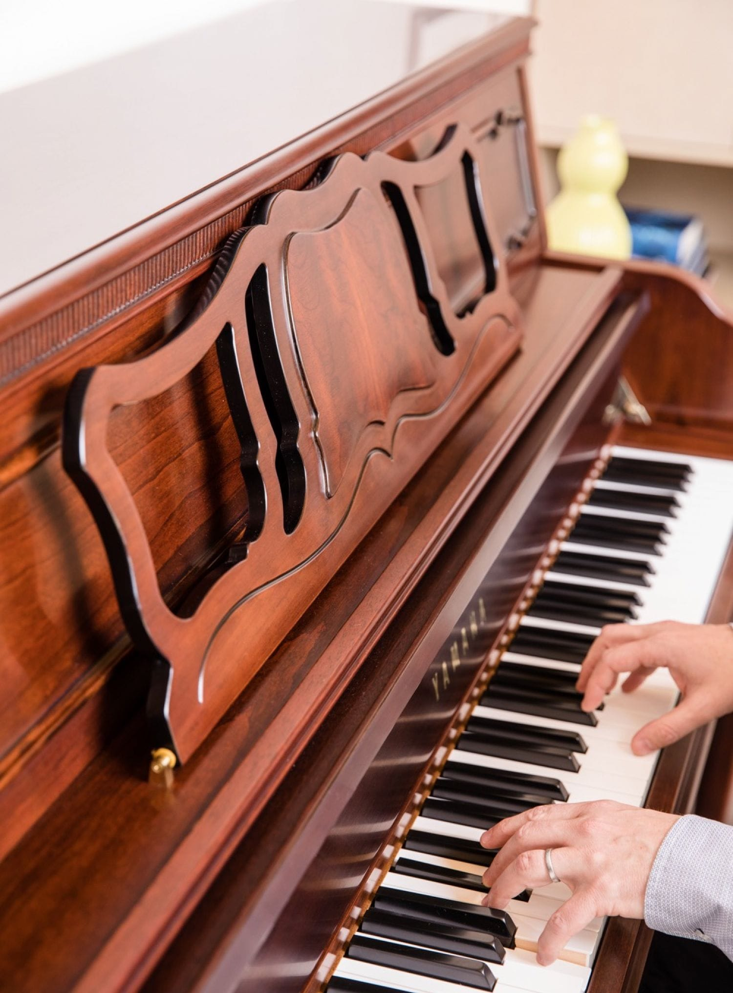 An adult male's hands playing the piano.