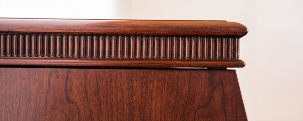 Closeup of the furniture type detailing of the wood case. This includes a border along top edge with a row of tiny posts.