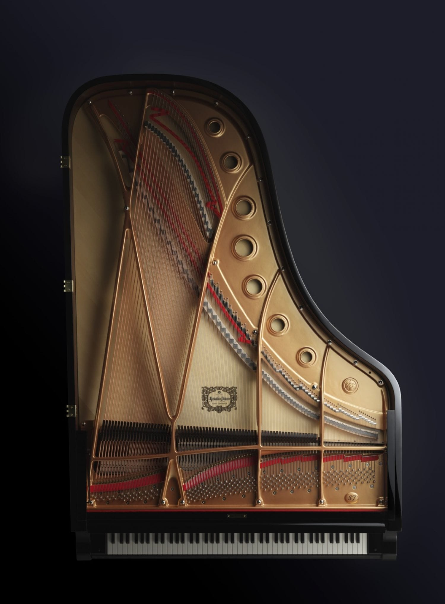 A Yamaha grand piano with lid removed and viewed from above to see entire interior.