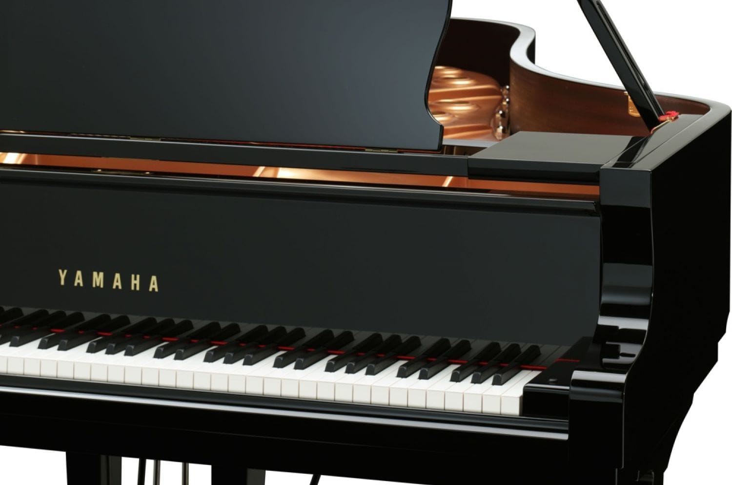 A view of a Yamaha grand piano's right side of the keyboard with lid open in background.