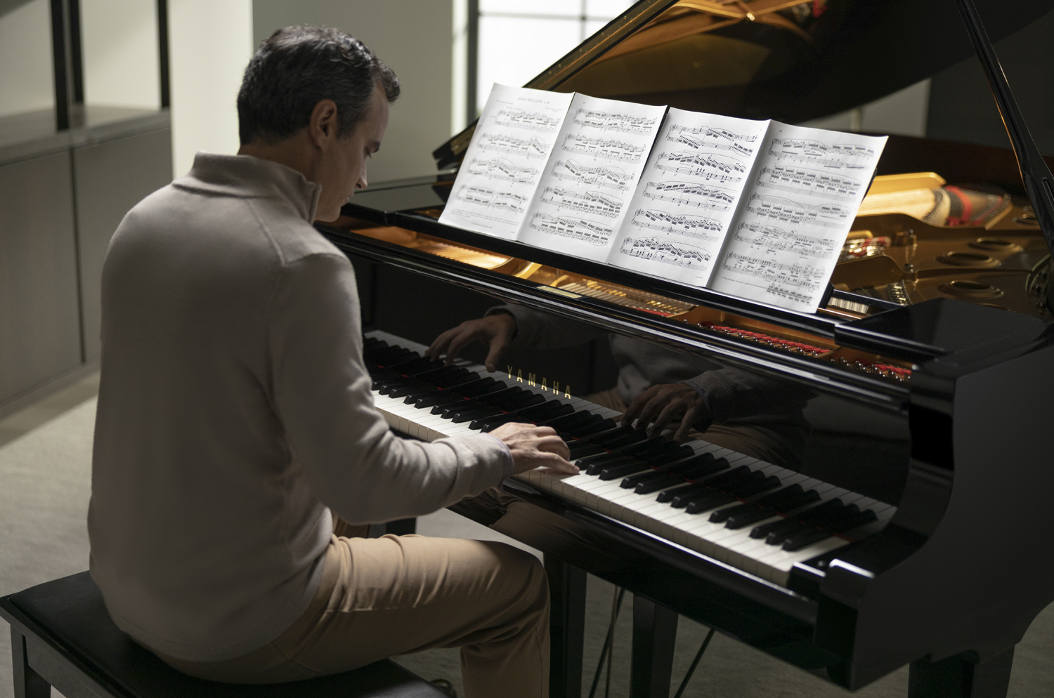 An older man in a suit playing a grand piano.