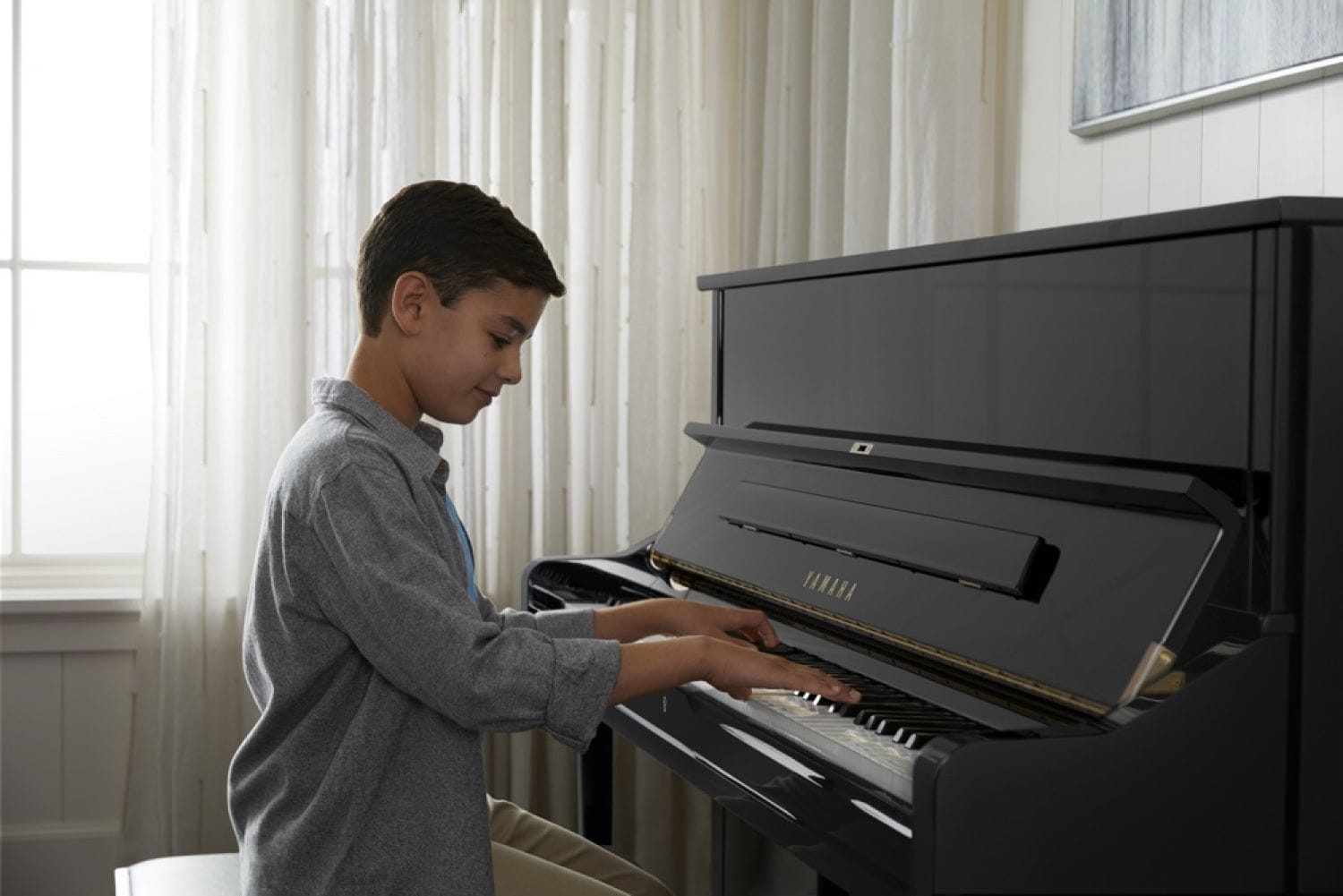 Young boy smiling as he plays a Yamaha upright piano in a living room setting.