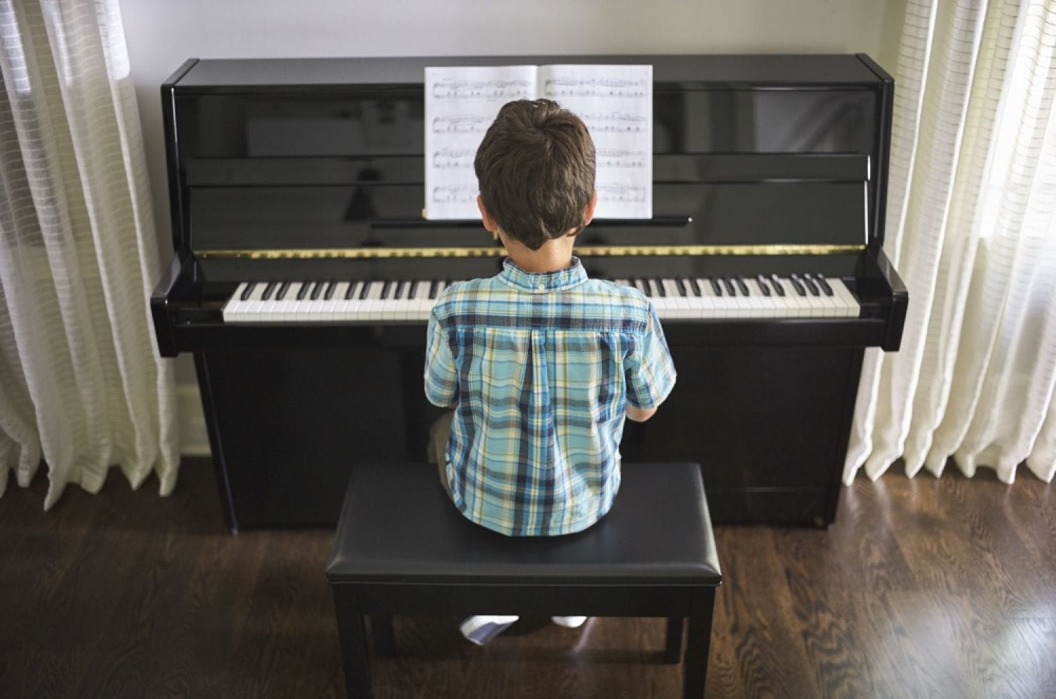 Small boy with back to camera as he is sitting at piano playing while looking at sheet music on ledge.