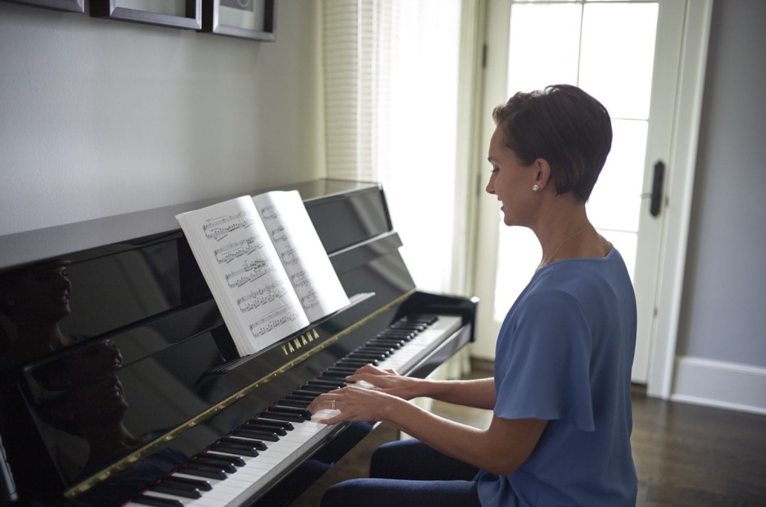 Woman in her early 30's in her living room playing an upright piano from book of sheet music.