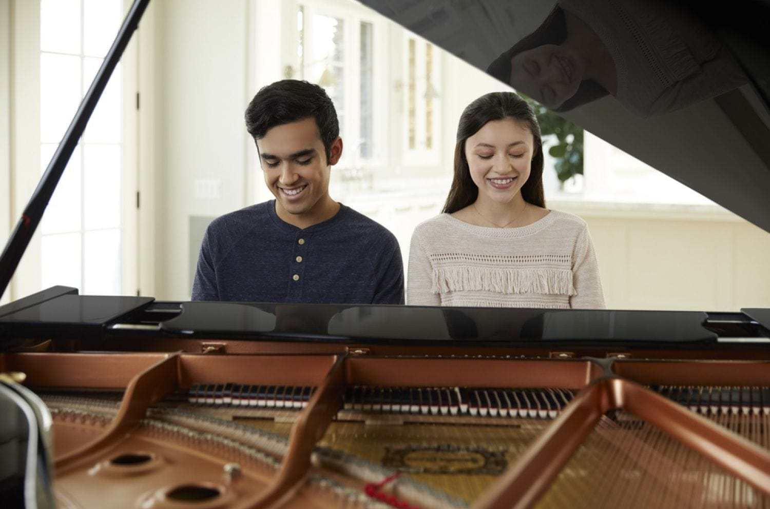 Young man and young woman seated side by side smiling and playing piano with lid open in foreground.