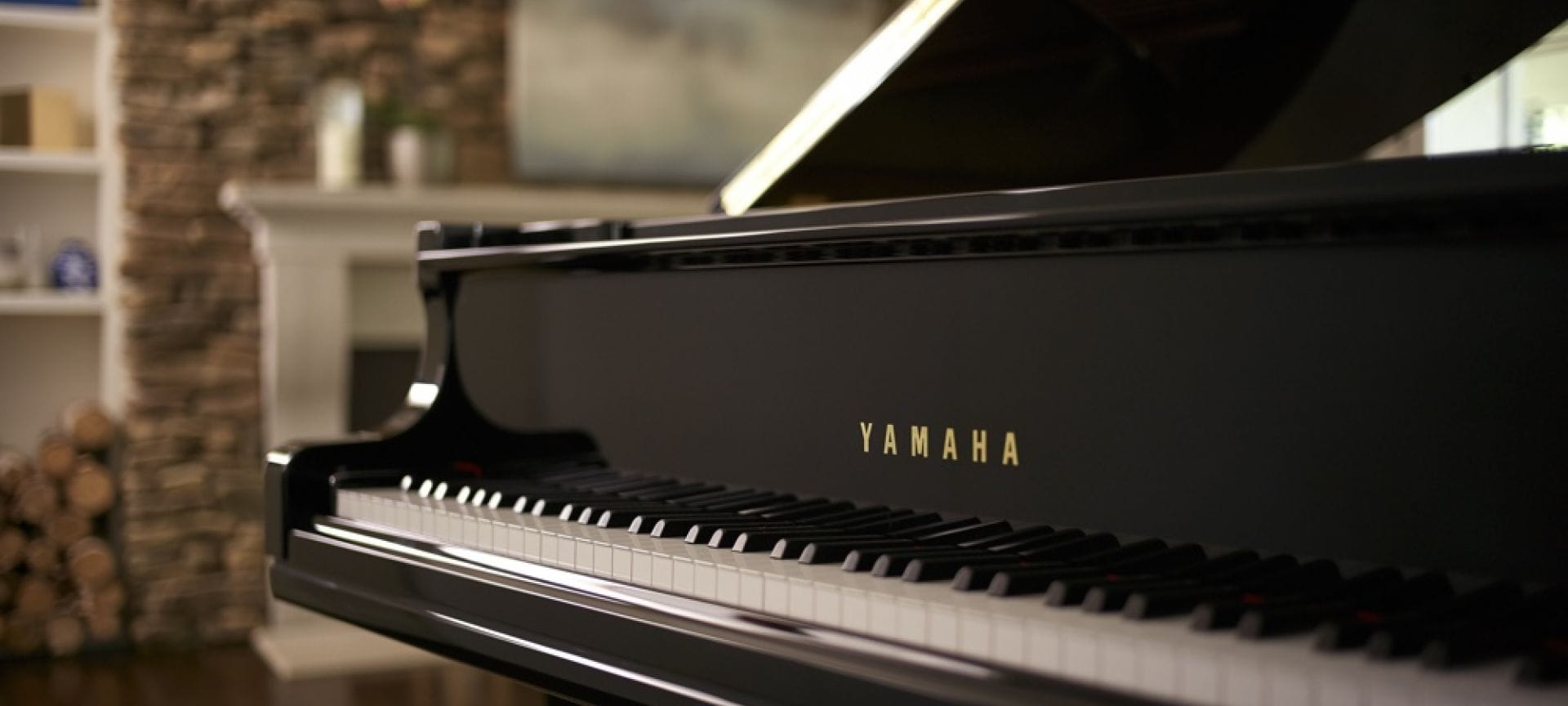 Close-up of Yamaha baby grand piano keys with lid open and fireplace in background.