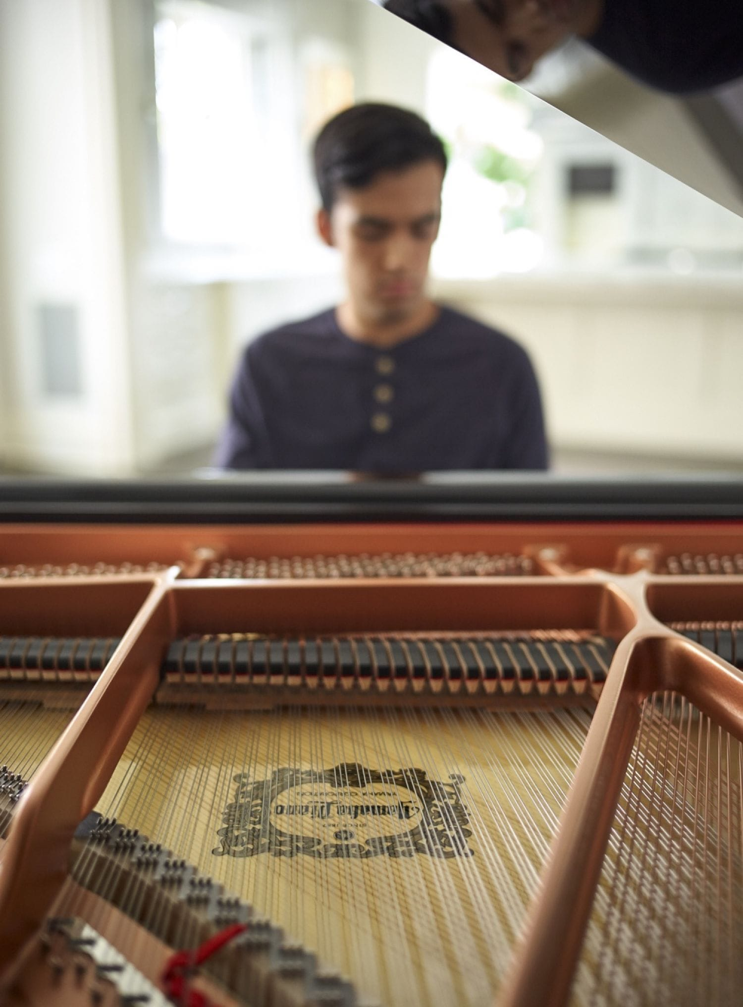Closeup of the inner workings of the piano with a young man seated at the far end focused on playing.