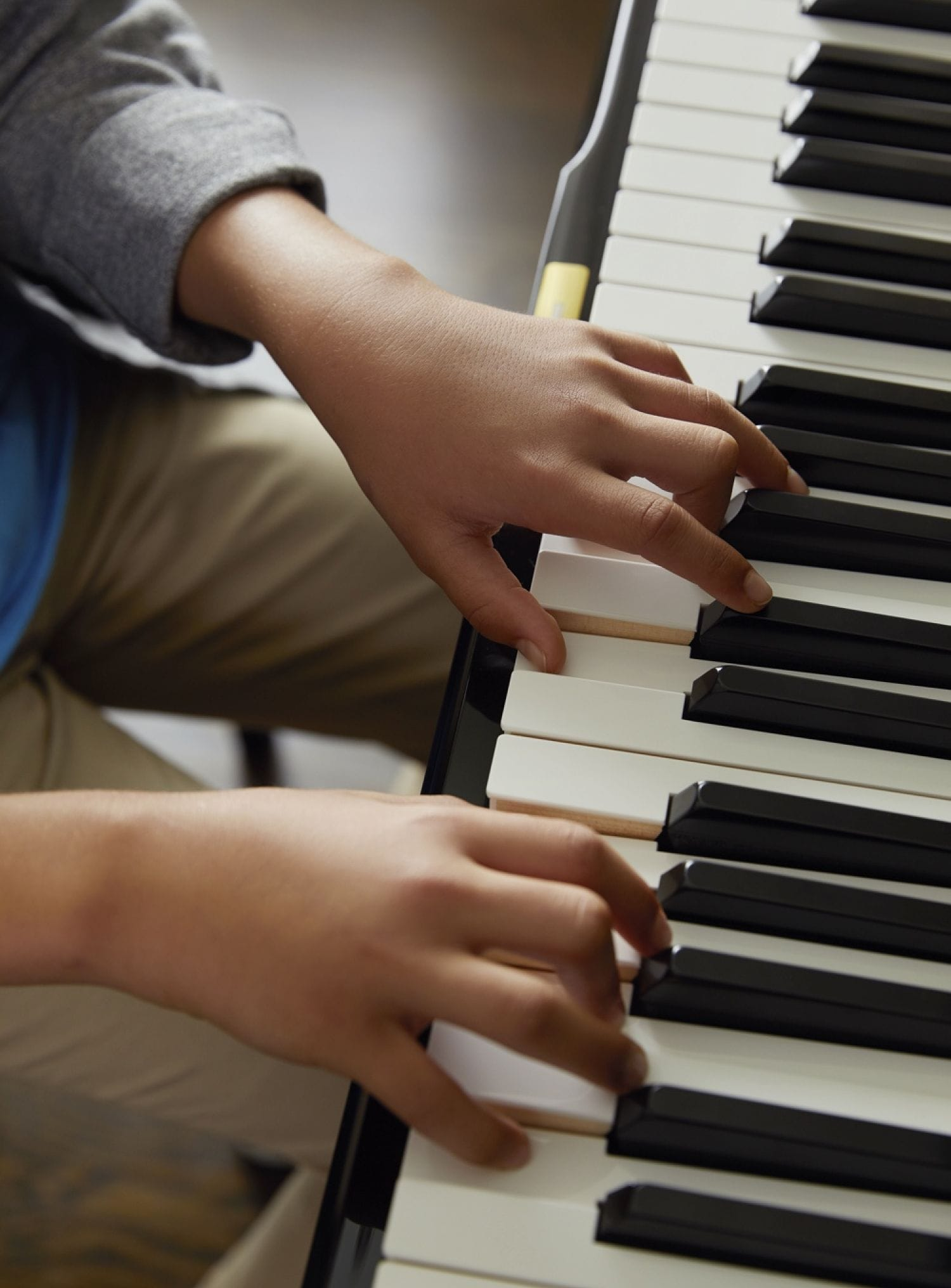 Young hands playing piano keys.