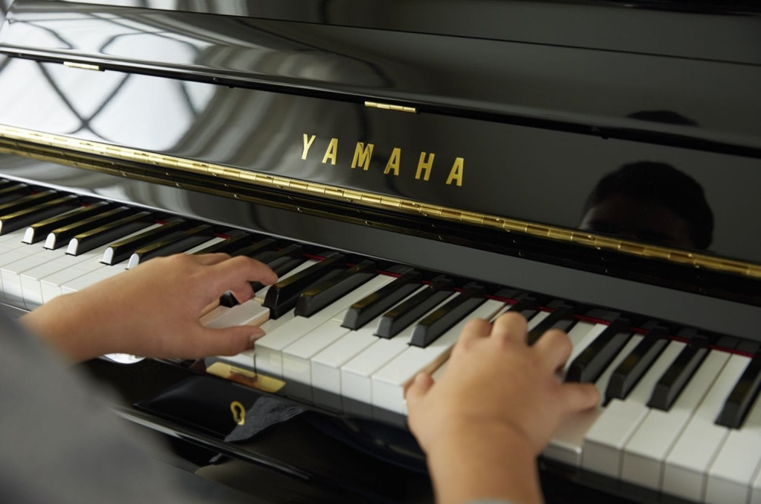 Child's hands playing a Yamaha upright piano.