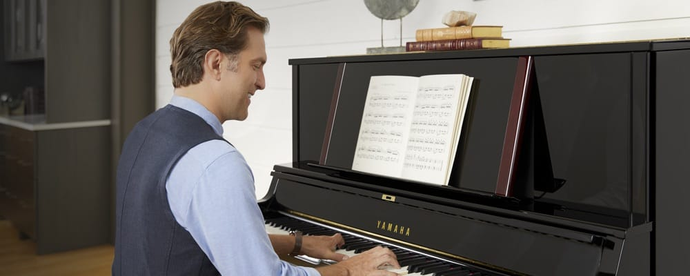 A man smiling as he plays from sheet music on a Yamaha upright piano in his living room.