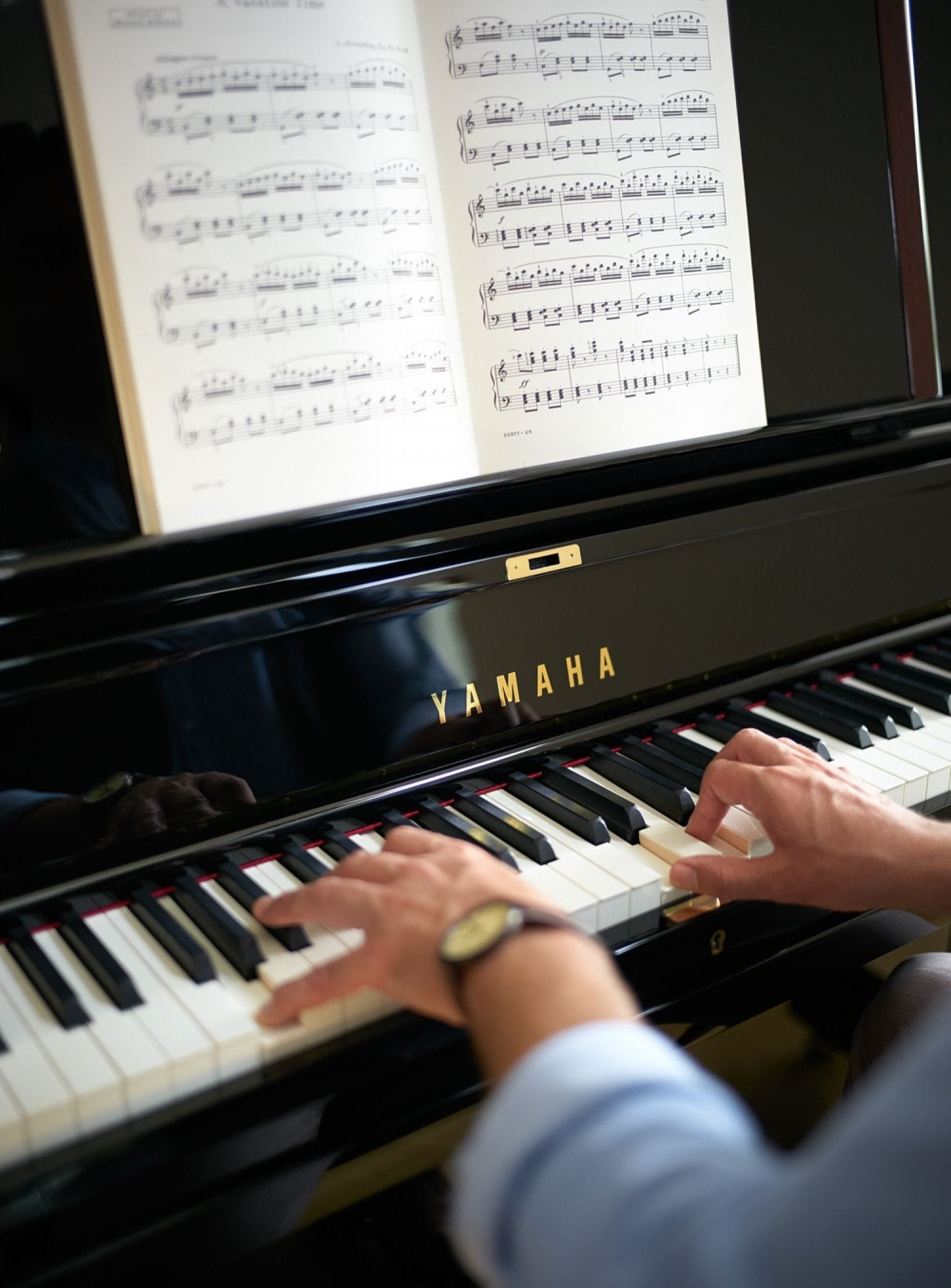 Closeup of man's hands as he plays a Yamaha piano from sheet music.