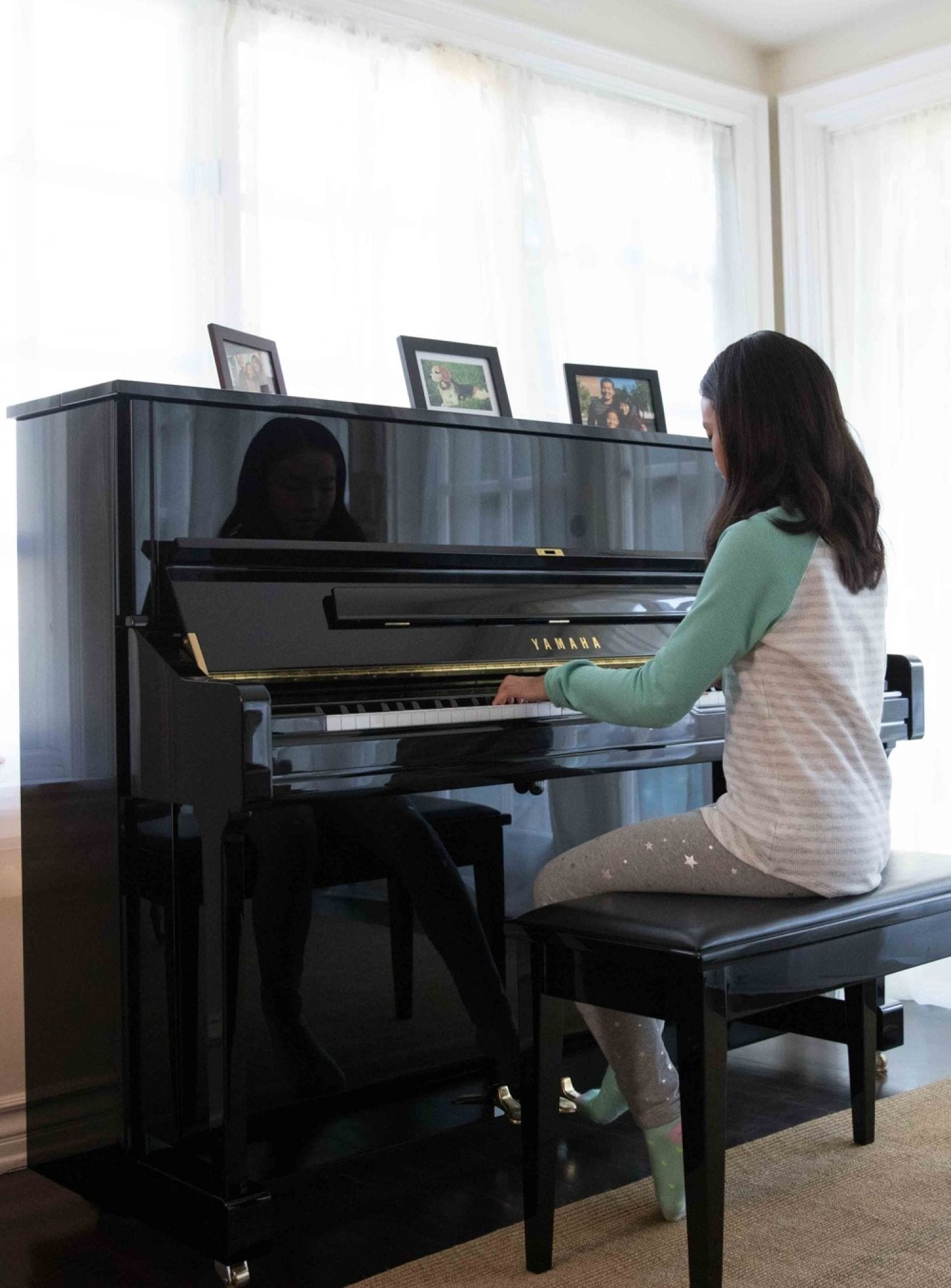Young girl in her living room playing a Yamaha upright piano.