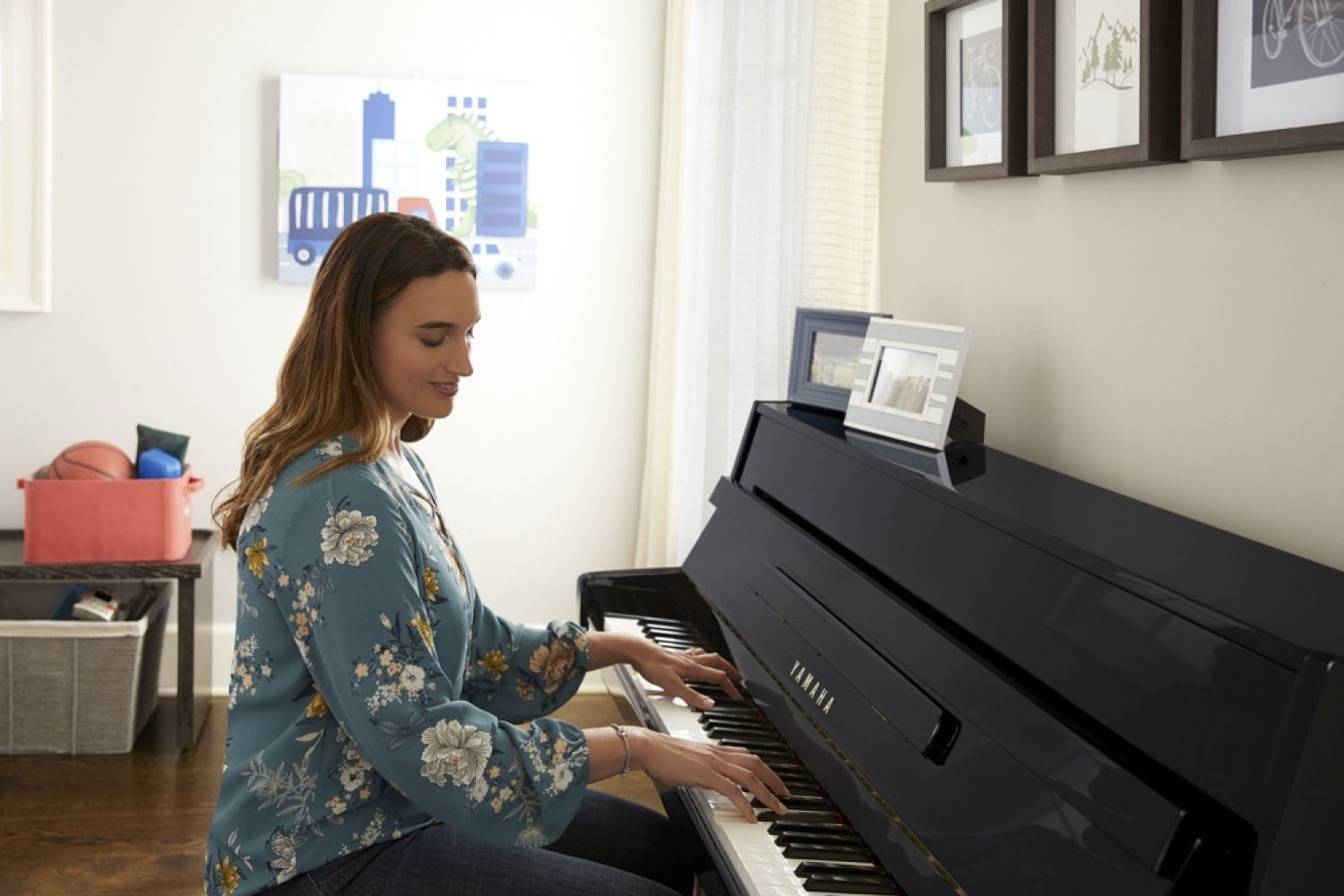 A woman approximately 30 years old with long hair and dressed casually smiling while she plays an upright piano with a lower profile back in what appears to be a kids' playroom in a home. There are kids drawings and toys in baskets in background and family pictures framed sitting on the back of piano.
