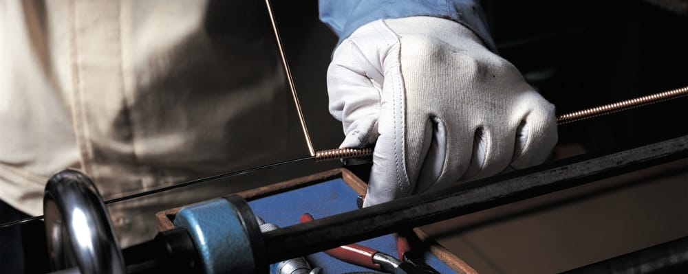 Closeup of gloved hands wrapping a piano wire that is taut.