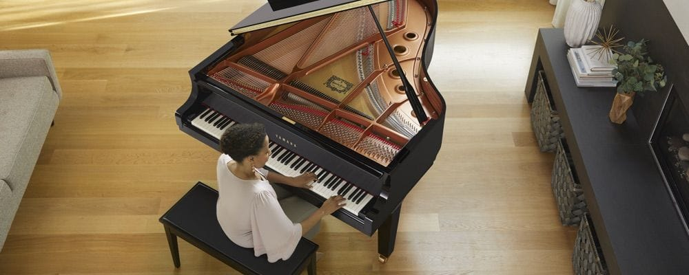 View from above as a woman plays a Yamaha grand piano in her living room.
