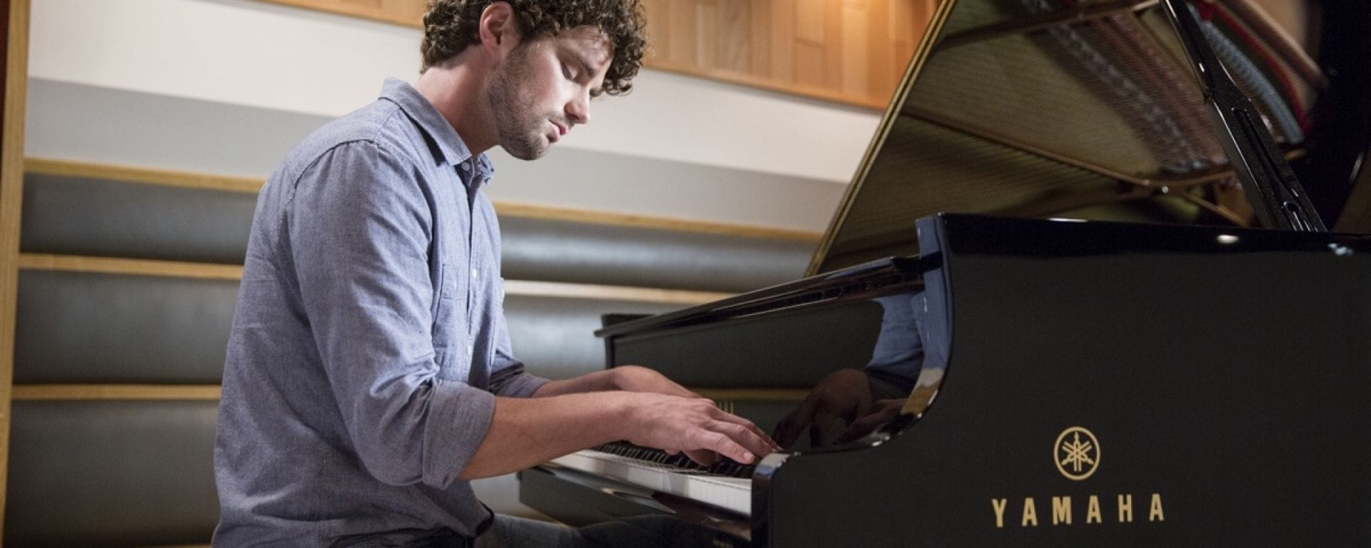 Man in his 20's dressed casually with curly hair and some facial hair playing a Yamaha piano.