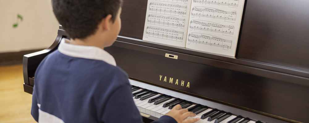 Young kid playing a piano.