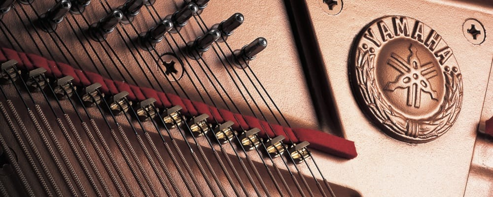 Closeup of soundboard and ribs with Yamaha logo (three intersecting tuning forks).