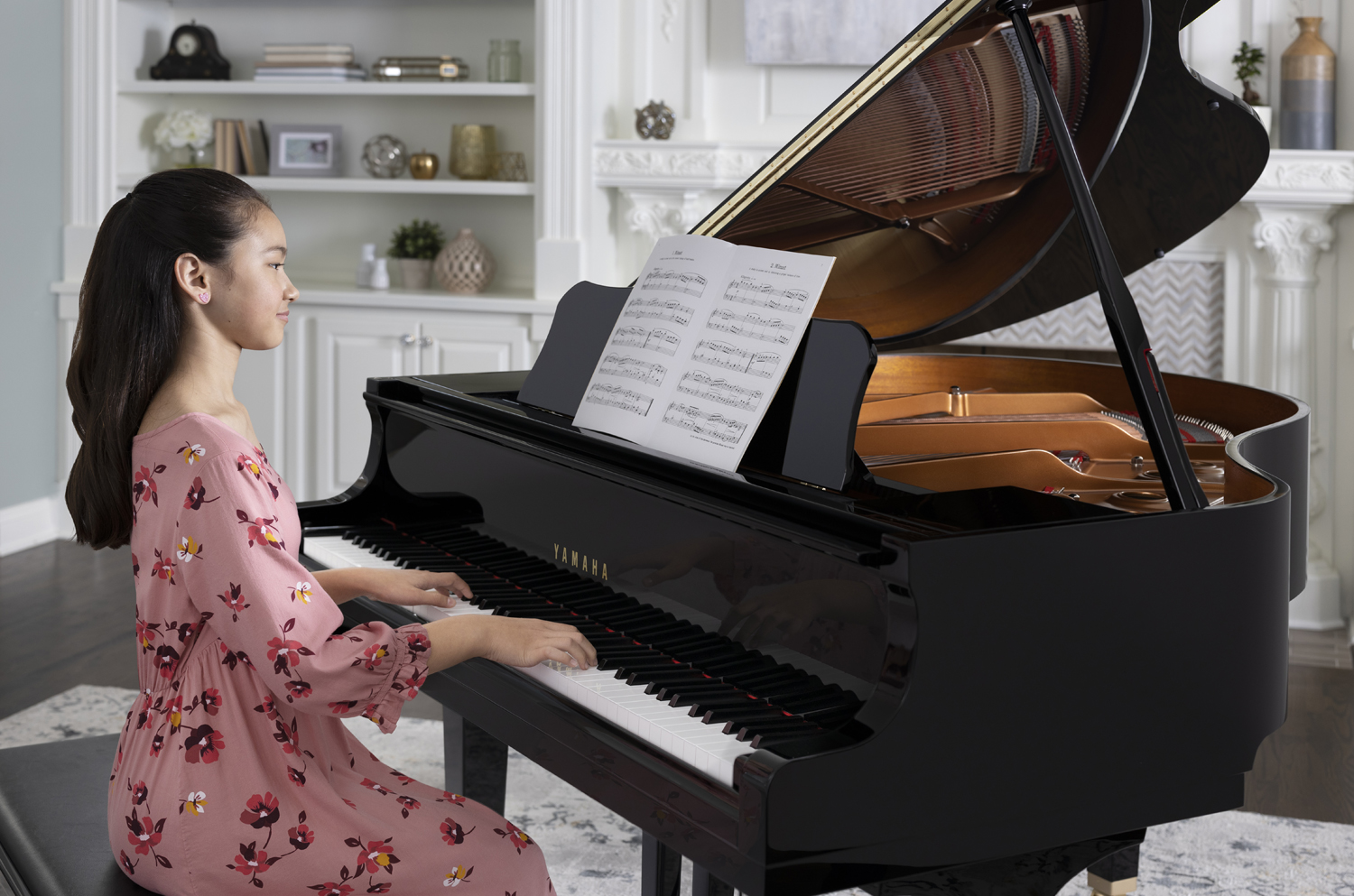 Young woman in casual clothes playing Yamaha baby grand from sheet music with fireplace and bookshelves in background.