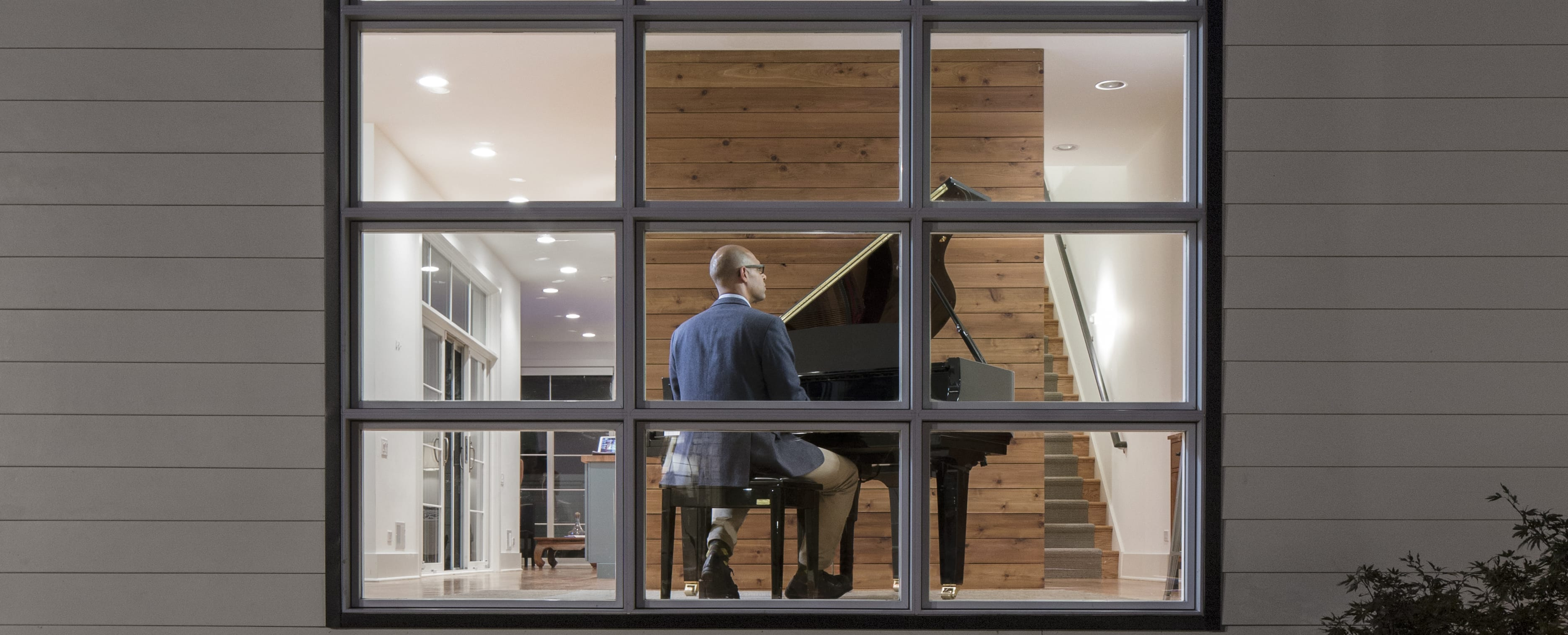 African American man in a sports jacket and slacks with his back to camera playing a baby grand piano in a modern house being viewed from outside through a 9-pane bay window.