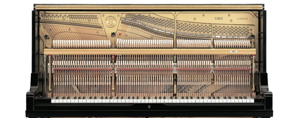 An upright piano with lid open displaying interior.