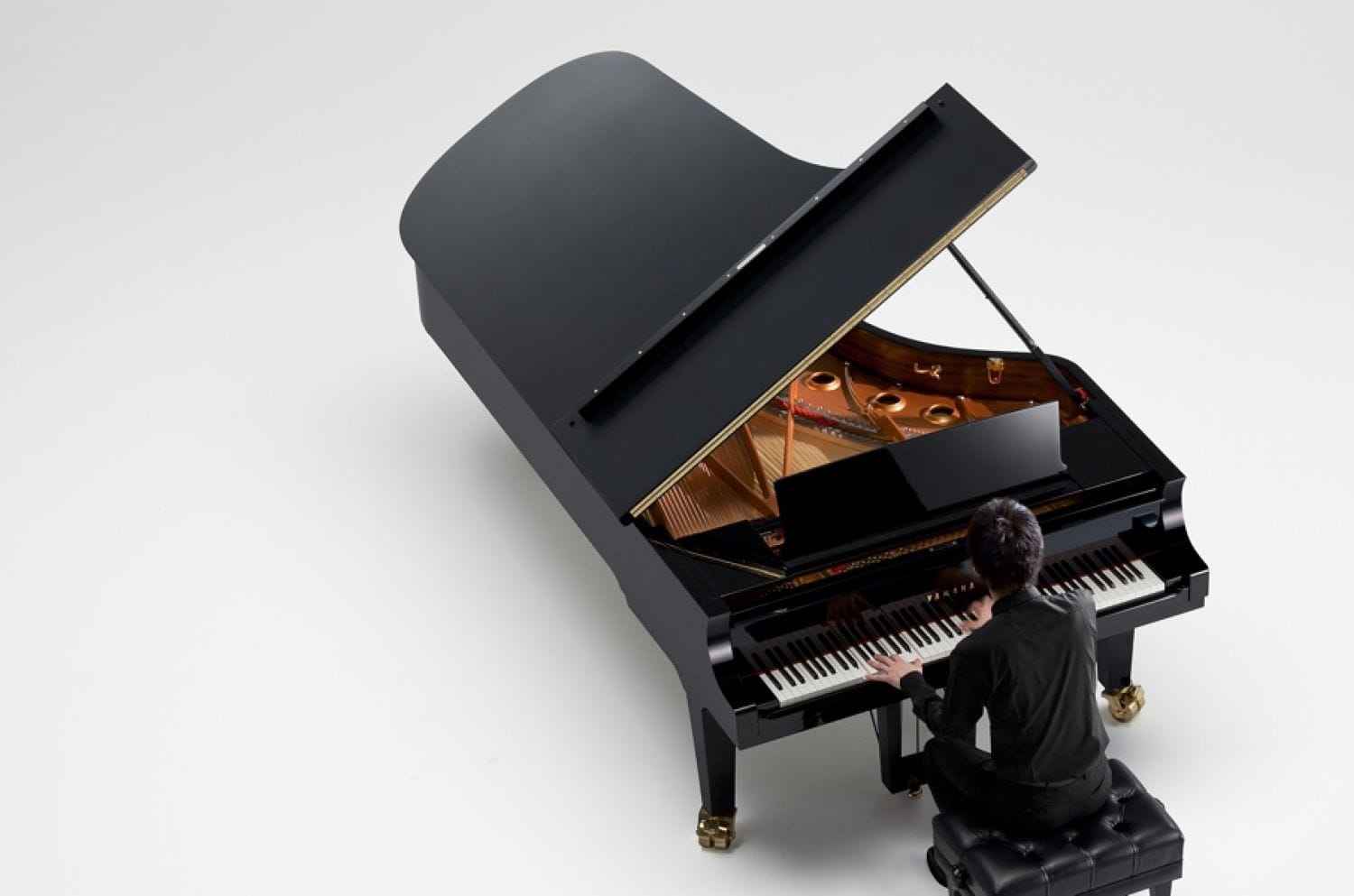 A woman playing a Yamaha concert grand piano with the lid open in a large empty space.