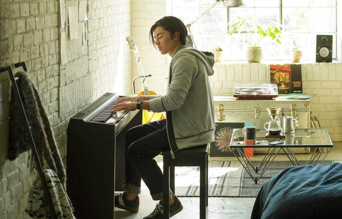 Young woman playing a Yamaha piano with a tablet-style screen above the keyboard which is providing information on the CFX Grand piano.
