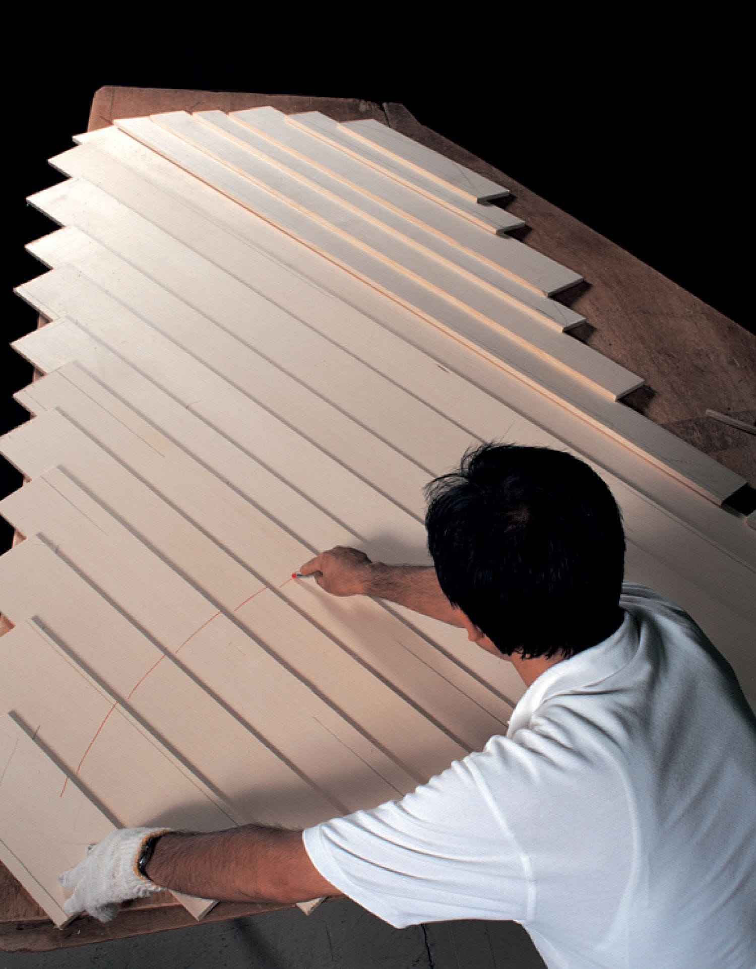 Craftsman drawing out the cutline on a set of overlapped, side by side wood boards.