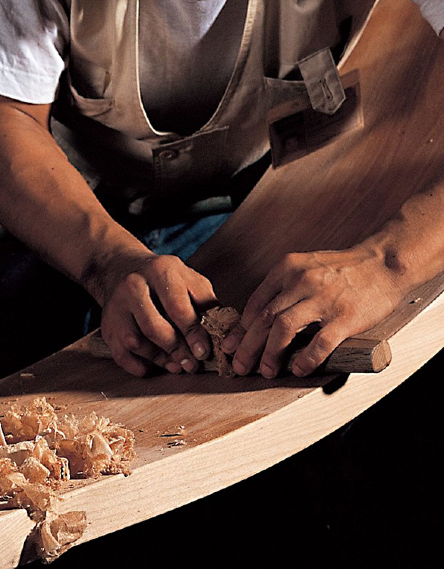 A craftsman's hands as he hand planes the wood for the edge.