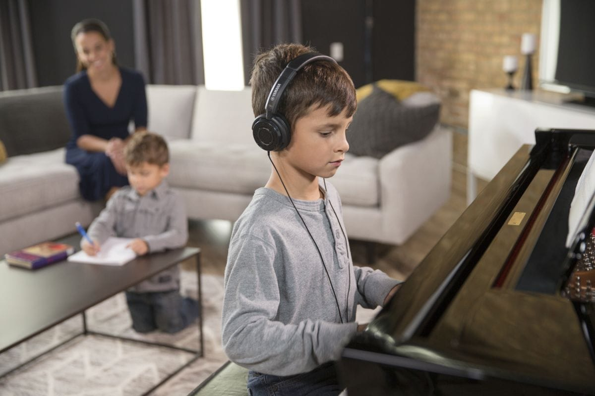 Young boy playing an upright piano in his living room wearing headphones while his mother and younger brother hang out undisturbed behind him.