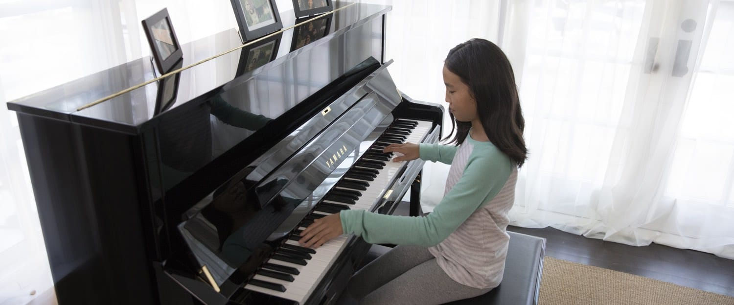 Young girl playing a Yamaha upright piano in her living room.