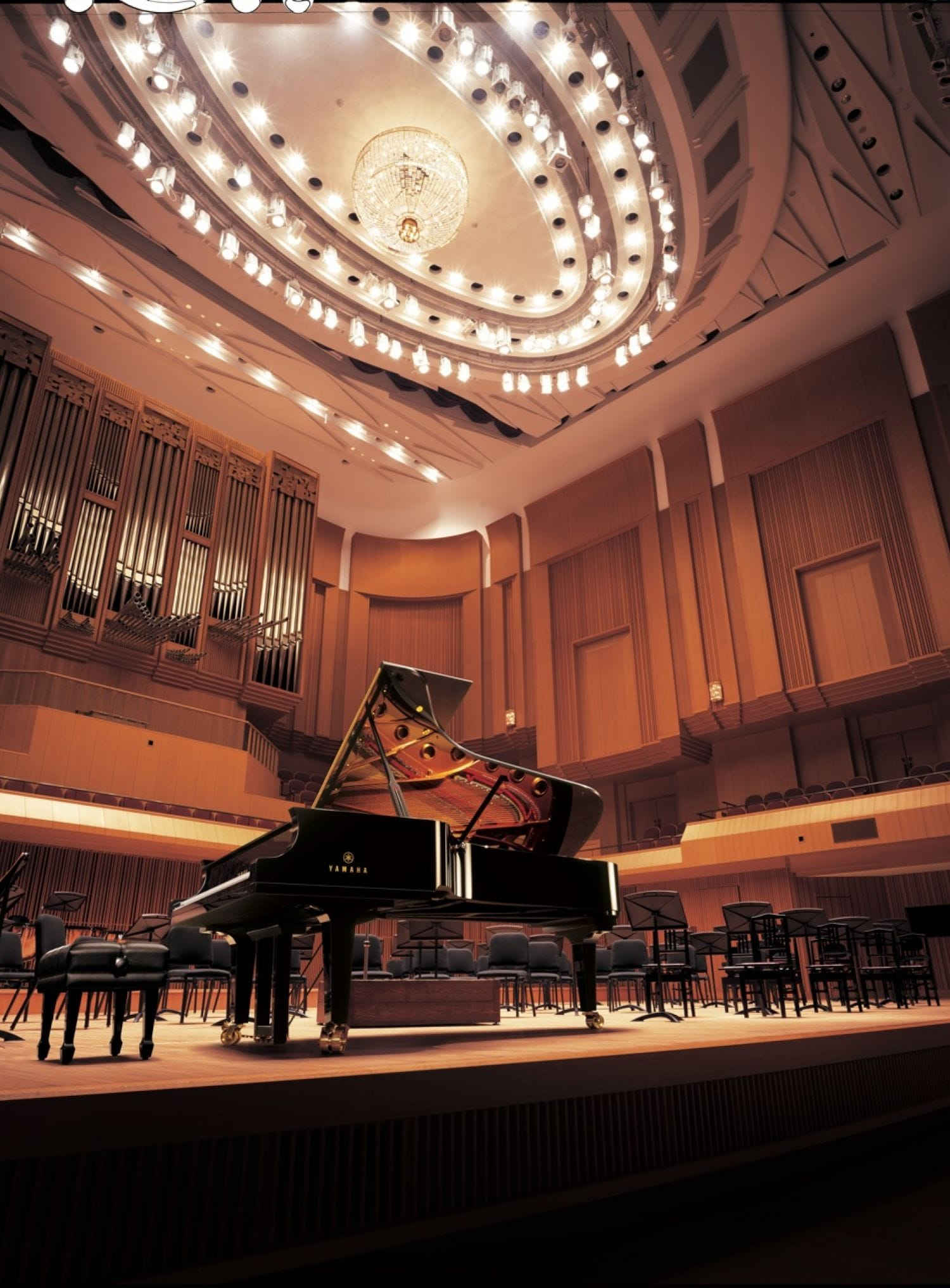 A Yamaha concert grand piano front and center on a fancy performance hall set for an orchestral performance.