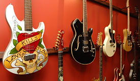 Red wall with hanging guitars